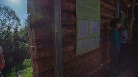 La chica joven muestra la trayectoria adentro a la casa de madera