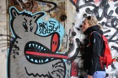 La chica joven muestra su lengua con las pinturas de pared (pintada) en fondo Fotografía de archivo