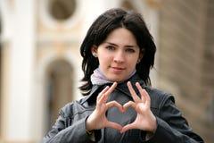 La chica joven muestra un símbolo del corazón Imagen de archivo libre de regalías