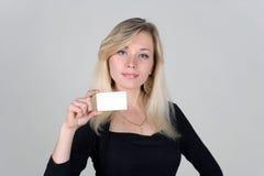 La chica joven muestra una tarjeta plástica en blanco Imágenes de archivo libres de regalías