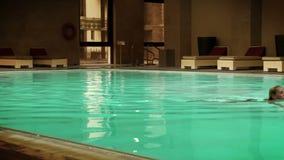La chica joven nada en la piscina interior de un hotel grande almacen de metraje de vídeo