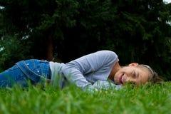 La chica joven pone en el estómago en la sonrisa de la hierba Fotografía de archivo
