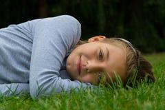 La chica joven pone a un lado en la hierba que sonríe pacífico Foto de archivo