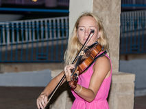 La chica joven por la tarde del verano juega para los transeúntes en el violín en la costa de Nahariya, Israel Fotos de archivo