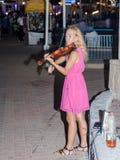 La chica joven por la tarde del verano juega para los transeúntes en el violín en la costa de Nahariya, Israel Imagen de archivo libre de regalías