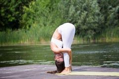 La chica joven practica la yoga en la orilla del lago, el concepto de disfrutar de la privacidad y de la concentración, luz del s foto de archivo