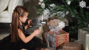 La chica joven preciosa encuentra su presente debajo del árbol de navidad metrajes