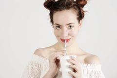 La chica joven preciosa está bebiendo con una paja con sonrisa inocente en su cara Imagenes de archivo