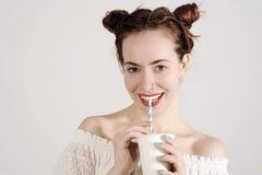 La chica joven preciosa está bebiendo con una paja con sonrisa inocente en su cara Fotografía de archivo