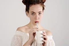 La chica joven preciosa está bebiendo con una paja Estudio tirado con el fondo ligero Foto de archivo