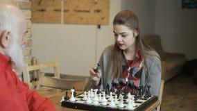La chica joven pregunta a su abuelo cómo jugar a ajedrez almacen de metraje de vídeo