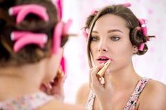 La chica joven que aplica el lápiz labial y que la hace compone listo Fotos de archivo