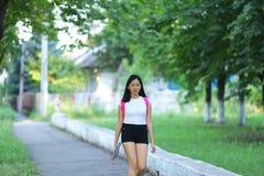 La chica joven que camina en el parque es paso Foto de archivo