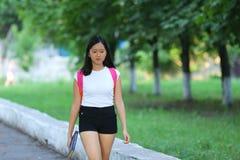 La chica joven que camina en el parque es paso que camina Imagenes de archivo