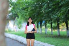 La chica joven que camina en el parque es paso que camina Imagen de archivo libre de regalías