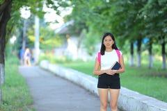 La chica joven que camina en el parque es paso que camina Foto de archivo