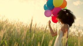 La chica joven que camina a través de un campo de trigo con color hincha durante puesta del sol almacen de video