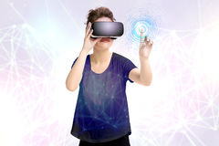 La chica joven que consigue experiencia usando los vidrios de las auriculares de VR, es lentes aumentadas de la realidad, estando Foto de archivo libre de regalías