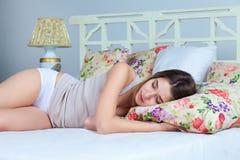 La chica joven que duerme en cama Fotos de archivo libres de regalías