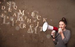 La chica joven que grita en el megáfono y el texto salen Fotografía de archivo