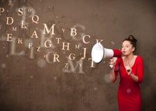 La chica joven que grita en el megáfono y el texto salen Imagenes de archivo