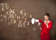 La chica joven que grita en el megáfono y el texto salen Imagen de archivo