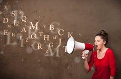 La chica joven que grita en el megáfono y el texto salen Foto de archivo libre de regalías