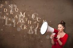 La chica joven que grita en el megáfono y el texto salen Imágenes de archivo libres de regalías