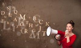 La chica joven que grita en el megáfono y el texto salen Foto de archivo