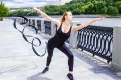 La chica joven que hace la gimnasia rítmica ejercita con la cinta al aire libre Fotos de archivo libres de regalías