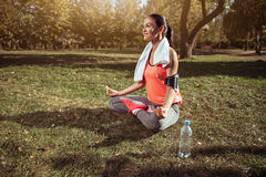 La chica joven que hace postura del loto de la yoga después de mañana ejercita Imagenes de archivo