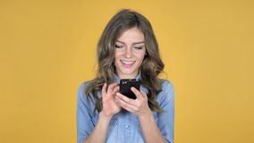 La chica joven que hojeaba Smartphone aisló en fondo amarillo almacen de video