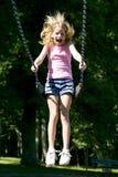 La chica joven que jugaba en un oscilación fijó en el parque Fotografía de archivo