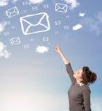 La chica joven que mira símbolo del correo se nubla en el cielo azul Imagenes de archivo