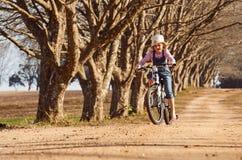 La chica joven que montaba su árbol del camino de tierra de la bici de la bicicleta abajo alineó la avenida Fotografía de archivo