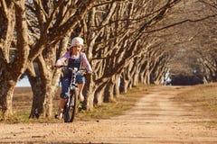 La chica joven que montaba su árbol del camino de tierra de la bici de la bicicleta abajo alineó la avenida Foto de archivo libre de regalías