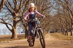 La chica joven que montaba su árbol del camino de tierra de la bici de la bicicleta abajo alineó la avenida Fotos de archivo libres de regalías
