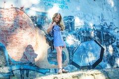 La chica joven que presenta contra una pared con la pintada, el Sun, vaqueros se coloca en las paredes pintadas Imagen de archivo