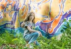 La chica joven que presenta contra una pared con la pintada, el Sun, vaqueros se coloca en las paredes pintadas Imagenes de archivo
