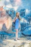 La chica joven que presenta contra una pared con la pintada, el Sun, vaqueros se coloca en las paredes pintadas Fotografía de archivo