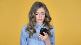 La chica joven que reaccionaba a la pérdida y usando Smartphone aisló en fondo amarillo metrajes