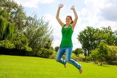 La chica joven que salta arriba en parque verde. Imágenes de archivo libres de regalías