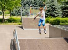 La chica joven que salta en el aire mientras que patinaje sobre ruedas Foto de archivo