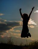 La chica joven que salta en la luz de la puesta del sol Fotos de archivo