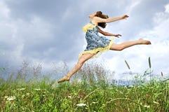 La chica joven que salta en prado Fotografía de archivo libre de regalías