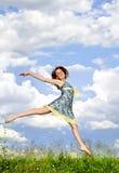 La chica joven que salta en prado Fotos de archivo