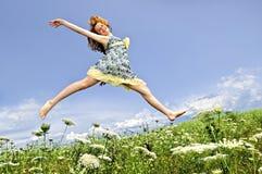La chica joven que salta en prado Imagen de archivo