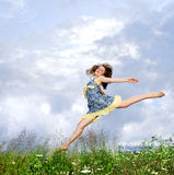 La chica joven que salta en prado Imagenes de archivo