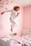 La chica joven que salta en su cama Foto de archivo