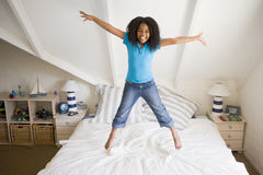 La chica joven que salta en su cama Fotos de archivo libres de regalías